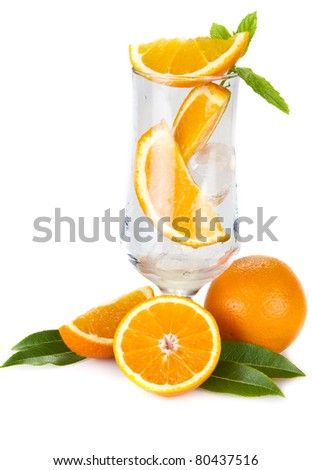 Pieces of orange and mint in the glass isolated over white - stock photo