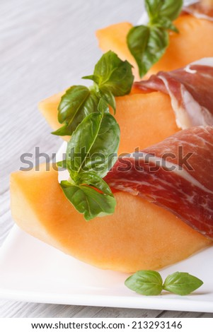 pieces of orange melon wrapped in prosciutto and green basil on a white plate on the table. vertical macro  - stock photo