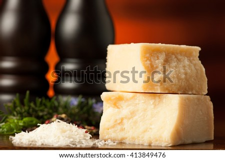 pieces of parmesan cheese on a wooden cutting board being cutt with cheese knife with spices  on a wooden restaurant table in background - stock photo