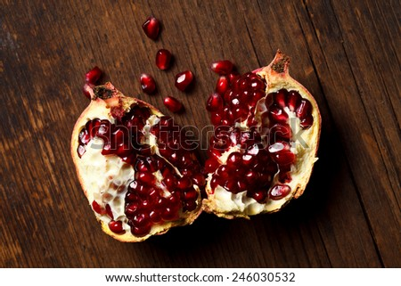Pieces of pomegranate with seeds falling out, rustic wooden background - stock photo