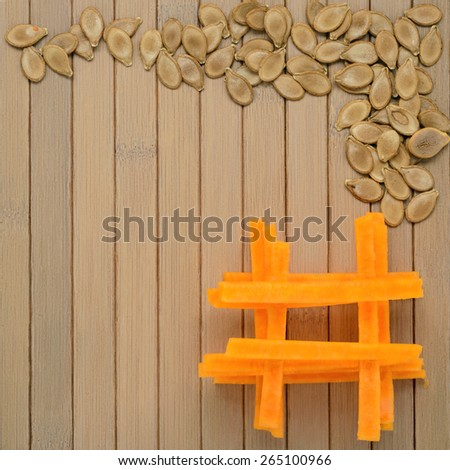 Pieces of pumpkin, pumpkin seeds and place for text on the wooden table - stock photo