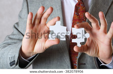 Pieces of puzzle in the hands of a business man. Closeup