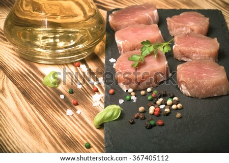 Pieces of raw meat on a plate of slate herbs spices and olive oil on a new burned wooden background. Selective focus. Toned. - stock photo