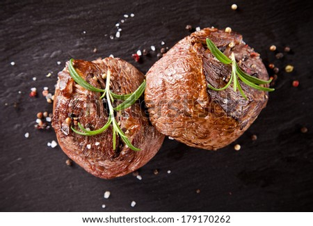 Pieces of red meat steaks with rosemary served on black stone surface. Shot from upper view - stock photo