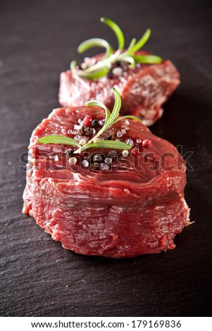 Pieces of red raw meat steaks with rosemary served on black stone surface. - stock photo