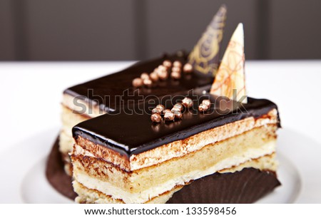 Pieces of sponge cake with chocolate on white table - stock photo
