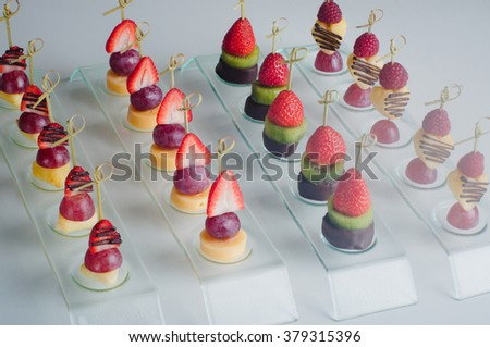 Pieces of strawberry, pineapple, grapes, kiwi, raspberry and cheese designed as a canape on the party table - stock photo