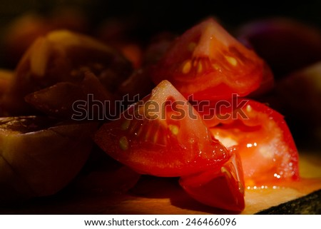 Pieces of tomatoes on a wooden board. Low light and shallow depth of field. Toned. - stock photo