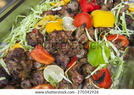 Pieces of veal tandoori meat with salad on display at an indian restaurant buffet