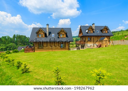PIENINY MOUNTAINS, POLAND - JUN 10, 2014: Traditional wooden mountain house on green field in summer, Szczawnica, Pieniny Mountains, Poland. Most houses are built from wooden logs in this area.