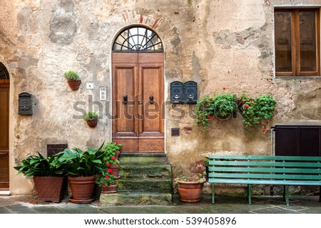 Pienza, Italy - November 21, 2016: House facade view with door, window and bench in Pienza, Italy on 21 of November, 2016. Pienza is the touchstone of Renaissance urbanism, UNESCO World Heritage Site.