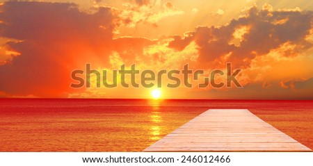 Pier and a sunset over the sea - stock photo
