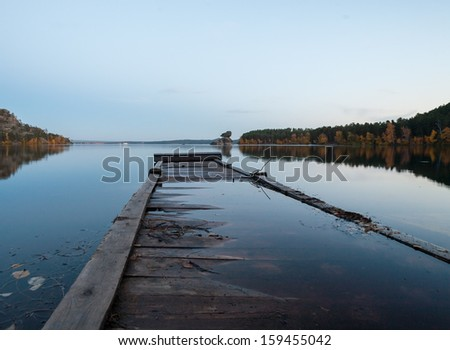 Pier and boat on the lake in the evening Barabbasi, now is quiet and peaceful, northern Kazakhstan. - stock photo