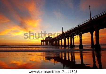Pier at Manhattan Beach in Los Angeles, California lit by a stunning sunset.