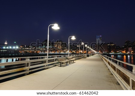 Pier at night with benches and lamps in the city. - stock photo