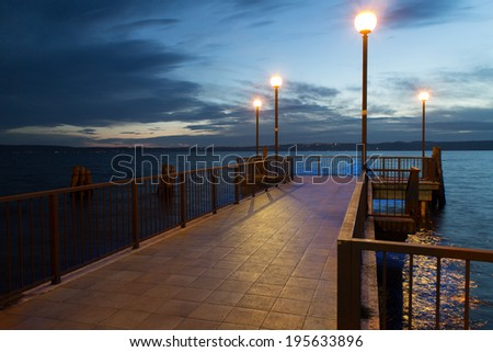 Pier at the dusk, with some lamps lighted - stock photo