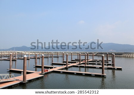 pier head with mooring cleats and berth of yacht marina on pontoons and position pilings mirrored in water with footpath between handrails on ladder from beach to the pier - stock photo