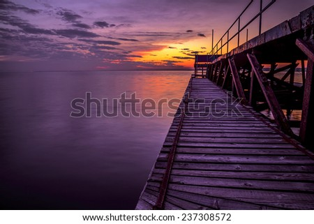 Pier in sea at sunset - stock photo