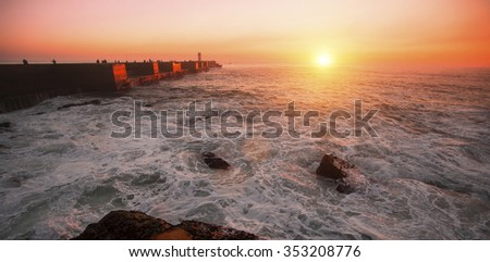 Pier in the Ocean, during amazing bloody sunset. - stock photo