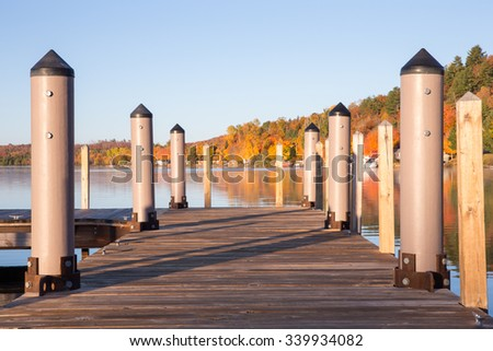 Pier leading to a smooth lake, colorful shoreline, and clear sky with copy space.  Selective focus on foreground elements of pier. - stock photo