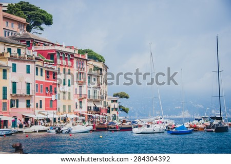 Pier of Portofino with tipical colored house and boats - stock photo