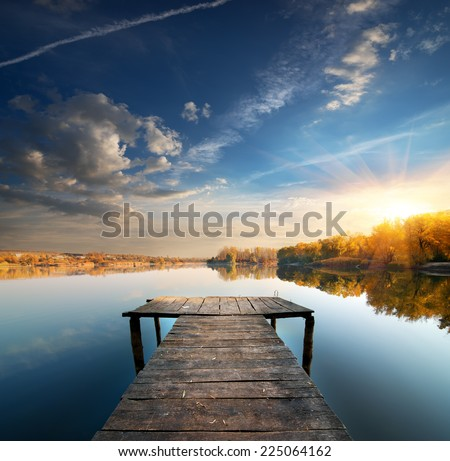 Pier on a calm river in the autumn - stock photo