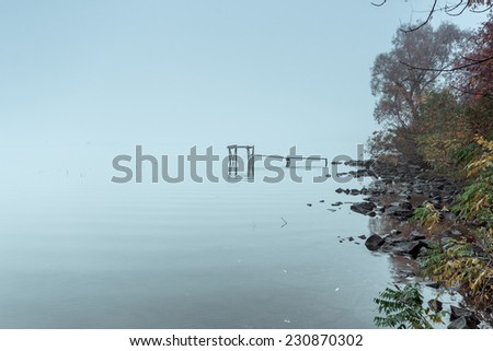 Pier on a calm river in the autumn. - stock photo