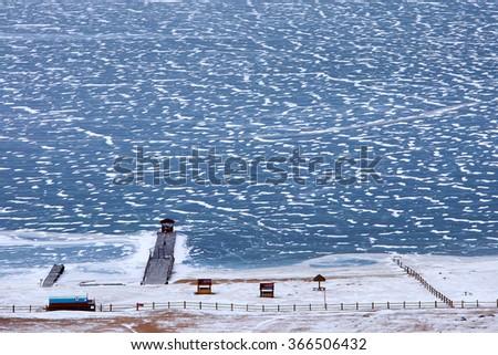 pier on the frozen Lake Baikal in December in the Irkutsk Region, Russia - stock photo