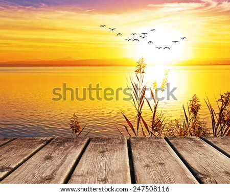 pier on the lake at sunset - stock photo