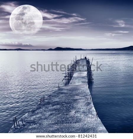Pier on the sea at night time. Moon in the sky - stock photo