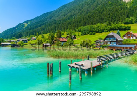 Pier on turquoise color Weissensee alpine lake in summer landscape of Alps Mountains, Austria - stock photo