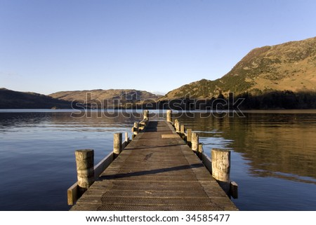 Pier on Ullswater in the Lake District, England, with mountain reflections - stock photo