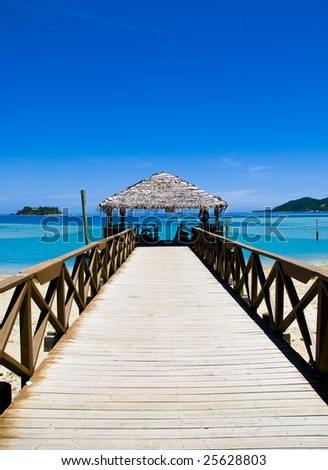 Pier or jetty on a tropical beach.  A vacation destination. - stock photo