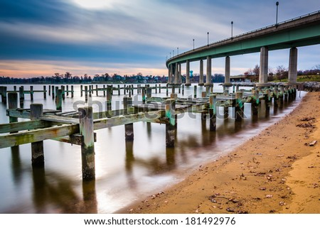 Pier posts in the Severn River and the Naval Academy Bridge, in Annapolis, Maryland. - stock photo