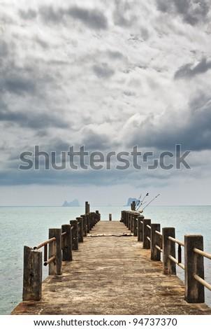 Pier under Dark Clouds - stock photo