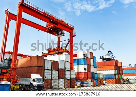Pier under the blue sky, cranes and containers. - stock photo