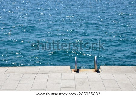 Pier with stairs on the sea - stock photo
