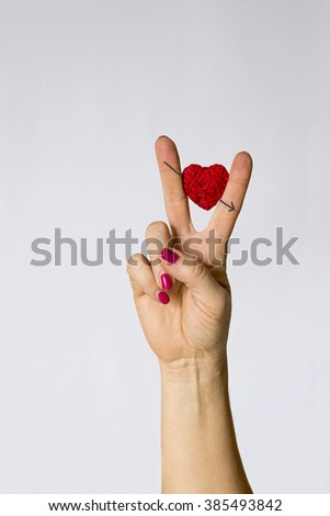 pierced heart, heart between the fingers/pierced heart between the fingers of the hand in the symbol of victory, the victory of love, a symbol of union and love - stock photo