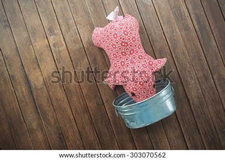 Pig doll eating food in metal container on wooden background. Toned image. - stock photo