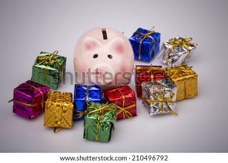 Pig money box between christmas gift on white background - stock photo
