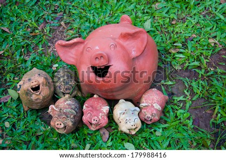 Pig statues laugh facing the same way on grass - stock photo
