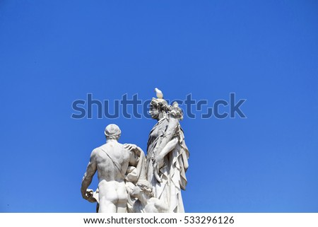 Pigeon on top of statue in front of Altar of the Fatherland with clear, blue sky background. Grand marble, classical temple honoring Italy's first king & First World War soldiers.