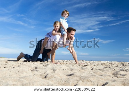 Piggy Back Fun on the Beach - stock photo