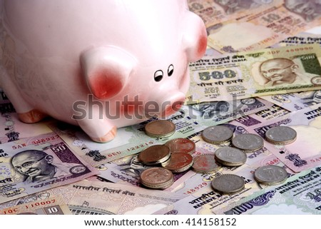 Piggy bank and Indian currency - stock photo