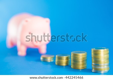 Piggy bank and money tower on blue background.Saving money Concept.Selective focus.