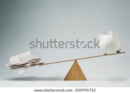 Piggy bank balancing on seesaw over a stack of bills - stock photo