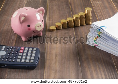 Piggy bank, calculator,reports and gold coins on wooden background
