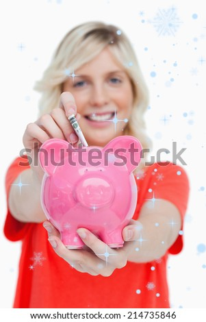 Piggy bank getting dollar notes from a young woman against snow falling - stock photo