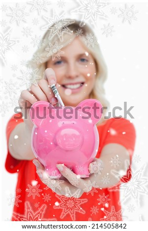 Piggy bank getting dollar notes from a young woman against snowflakes - stock photo