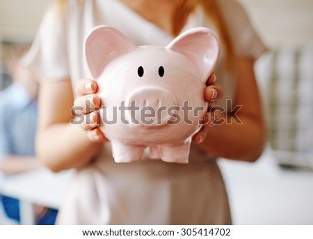 Piggy bank held by female